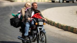 "Displaced Syrians ride a motorcycle fleeing Turkey""s military assault on Tal Abyad on 11 October"