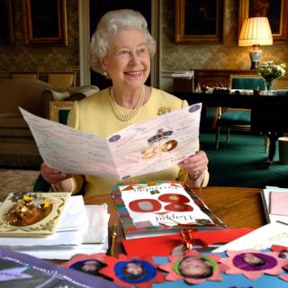 Queen reading cards sent to her for her 80th birthday