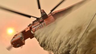 A helicopter drops fire retardant in Balmoral, 150 kilometres southwest of Sydney