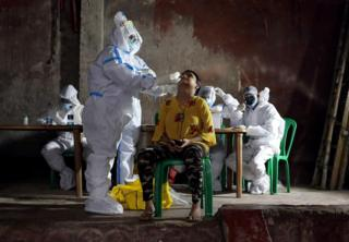 in_pictures A healthcare worker wearing personal protective equipment takes swab from a woman
