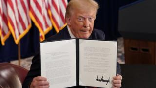 US President Donald Trump shows signed executive orders for economic relief