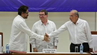 Colombia's Farc lead negotiator Ivan Marquez (L) and Colombia's lead government negotiator Humberto de la Calle (R) shake hands while Cuba's Foreign Minister Bruno Rodriguez looks on, after signing a final peace deal in Havana, 24 August 2016