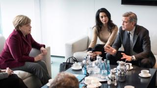 Handout picture showing German Chancellor Angela Merkel (2-L) receiving British human rights barrister Amal Clooney (C) and US actor George Clooney (12 Feb)
