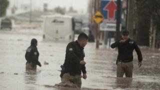 Police officers wade through severe floods, caused by heavy rains, affecting the city of Saltillo in the northern state of Coahuila, Mexico 26 July 2020