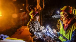 A child sits on a car in Lesbos