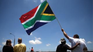 Des personnes tenant le drapeau de l'Afrique du Sud