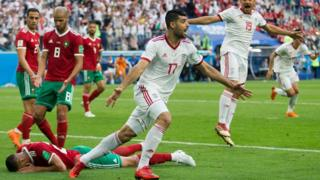 Iranian players celebrate after Morocco's Aziz Bouhaddouz scores an own goal in the 2018 World Cup