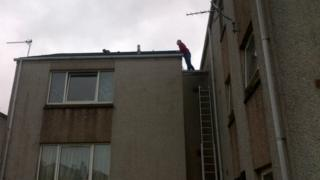 Cat being coaxed off roof in Stornoway