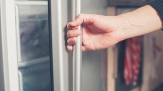 man opens fridge door