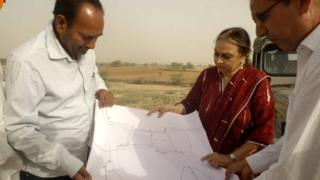 Amla Ruia with two engineers looking at plans outside in dry terrain