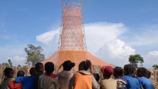 Niños frente a una torre de Warka Water