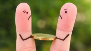 عملة معدنية بين إصبعين