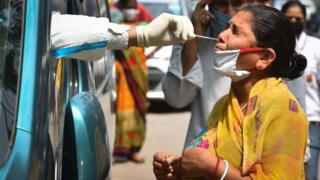 A health worker of Special Mobile Surveillance team in PPE coveralls collects a swab sample from a woman for Covid-19 rapid antigen test, at Model Town, on July 15, 2020 in New Delhi, India