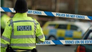 police in front of crime scene tape