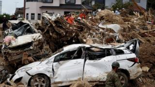Carro destruído em meio a destroços causados por chuvas torrenciais no Japão