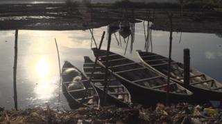 Fishing canoes on polluted creek