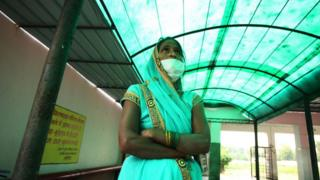 Relative of a patient suffering from Tuberculosis standing outside of a government hospital.
