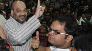 Indian politician and former Gujarat minister Amit Shah (L) and his son Jay celebrate on his arrival at his residence after his release from Sabarmati Central Jail in Ahmedabad late on October 29, 2010.