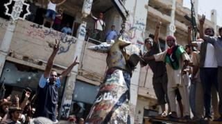 Rebels celebrate as they tear down 'hand crushing a plane' statue in Colonel Gaddafi's compound in Tripoli