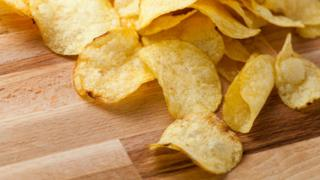"A stock image of crisps (or ""potato chips"" in some places) spilling across a wooden table."