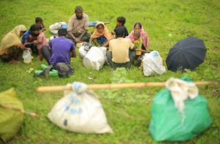 A Rohingya family sit in a field for a much-needed meal