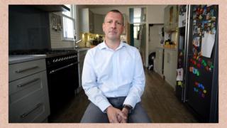Matt Merry, em foto recente, sentado em meio a móveis e utensílios na cozinha de casa. Ele espera justiça para as pessoas que, como ele, tiveram o sangue contaminado