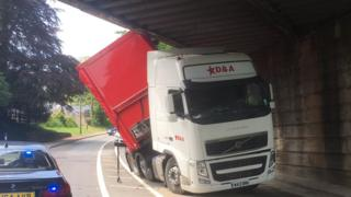 A lorry stuck under a bridge