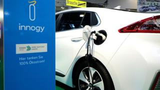 An electric car connects with a charger during a motor show in the western German city of Essen