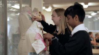 Children pinning material on a mannequin