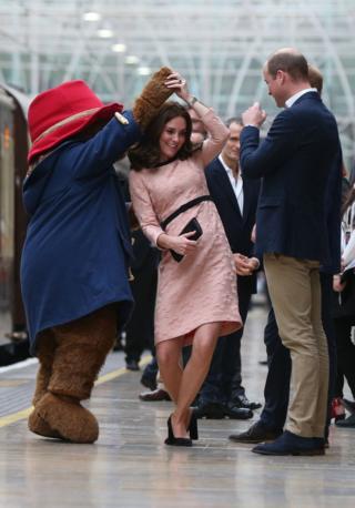 The Duchess of Cambridge dances with a costumed figure of Paddington Bear.