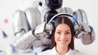 Smiling robot putting headphones on smiling woman