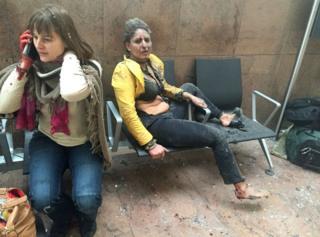 Dos mujeres cubiertas de polvo, una de ellas con el rostro ensangrentado, tras las explosiones en el aeropuerto de Bruselas