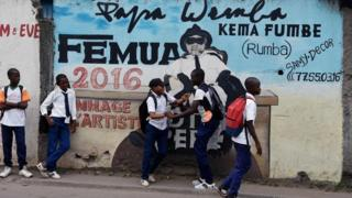 Youngsters stand next to a mural in tribute to Congolese rumba star Papa Wemba at Anoumabo district of Abidjan, Ivory Coast - Monday 20 February 2017