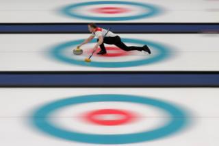 Magnus Nedregotten slides along the ice whilst Curling