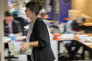 Johanna Stiles carries vote-by-mail ballots after the Leon County, Florida