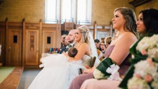Christina Torino-Benton breastfeeds her child during her wedding ceremony.