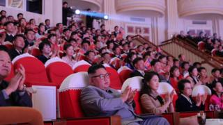 A crowded theatre claps at something out of view - but in the front row sits North Korean leader Kim Jong Un, but Kim Kyong Hui can be seen seated two places to his left