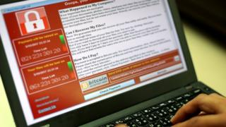 A programmer shows a sample of the WannaCry locked encryption page on a laptop