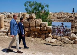 Prince William, Duke of Cambridge and Crown Prince Hussein of Jordan walk past an enlarged photo of Catherine, Duchess of Cambridge in her youth with her father on a family holiday