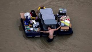 Residents wade with belongings in Houston