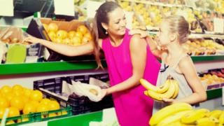 Woman and daughter shopping for bananas