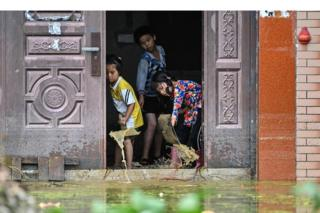Children remove water from inside their house in Longkou village due to torrential rains in Poyang county, Shangrao city, in China's central Jiangxi province on 16 July 2020