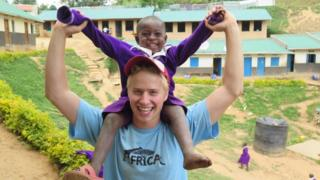 Edward Senior during his gap year in Africa. He has a young African boy on his shoulders. Both are smiling.