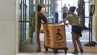 Zoo workers push boxes with animals in