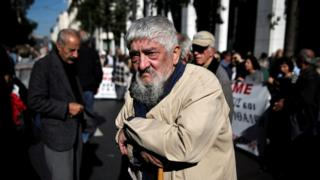 A Greek pensioner leans on a shepherd's crook during a demonstration against planned pension cuts in Athens, Greece, 3 November 2016