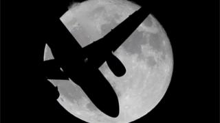 Aircraft in front of moon