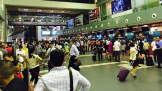 Passengers crowd at check-in counters at Noi Bai Airport in Hanoi, Vietnam Friday, July 29, 2016
