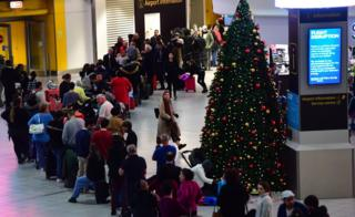 A queue of passengers next to a Christmas tree