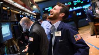 Imagem mostra homem sorrindo na bolsa de valores de Nova York