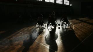 Atletas paralímpicos practican baloncesto.